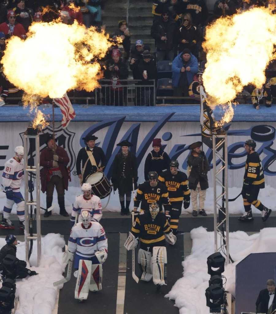 Flame towers ignite as the Montreal Canadiens, left, and Boston Bruins, right, file towards the ice prior to the NHL Winter Classic hockey game at Gillette Stadium in Foxborough, Mass., Friday, Jan. 1, 2016.
