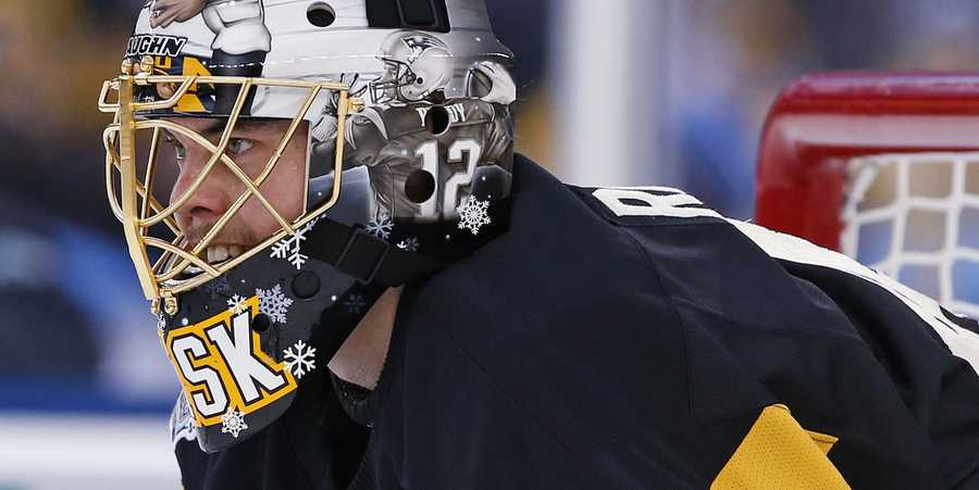With his mask adorned with an image of New England Patriots quarterback Tom Brady, Boston Bruins goalie Tuukka Rask waits for play to resume during the first period of the NHL Winter Classic hockey game against the Montreal Canadiens at Gillette Stadium, home of the Patriots, in Foxborough, Mass., Friday, Jan. 1, 2016.