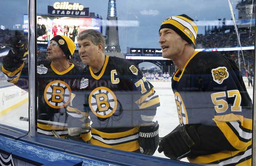 Former Boston Bruins', from left, Ken Linseman, Ray Bourque and Steve Heinze search for people in the stands before an outdoor hockey game against fellow alumni from the Montreal Canadiens at Gillette Stadium in Foxborough, Mass., Thursday, Dec. 31, 2015, where the Bruins will play the Canadiens in the NHL Winter Classic on Friday.
