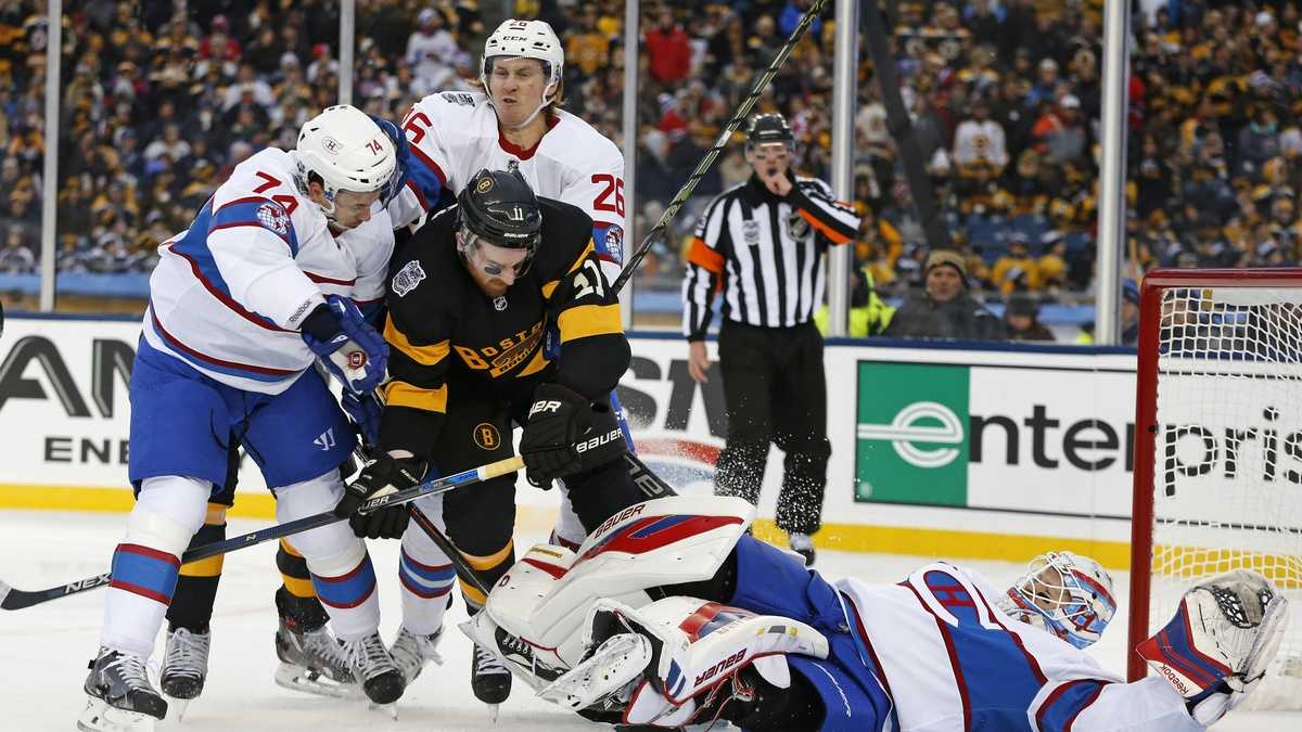 Boston Bruins right wing Jimmy Hayes (11) is cleared from the crease by Montreal Canadiens defensemen Alexei Emelin (74) and Jeff Petry (26) as goalie Mike Condon covers the puck on a save during the second period of the NHL Winter Classic hockey game at Gillette Stadium in Foxborough, Mass., Friday, Jan. 1, 2016.