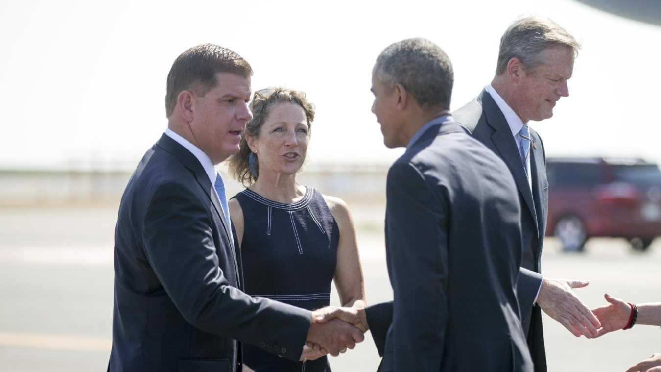 President Barack Obama is greeted by Boston Mayor Marty Walsh, left, Massachusetts Gov. Charlie Baker, right, and his wife Lauren Baker, center, as he arrives at Boston Logan International Airport in Boston.