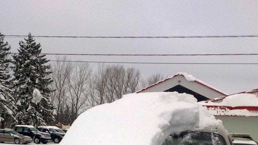 This Tuesday, Jan. 19, 2016 photo provided by the Ontario Provincial Police shows a snow covered vehicle in Brussels, Ontario. An 80-year-old man has been charged after driving the car that was almost completely covered in snow with only the driver's side windshield visible.