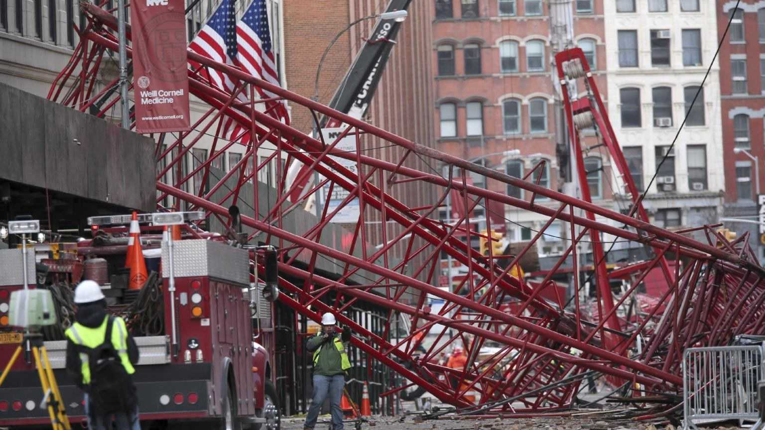 Firefighters and construction crews work on clearing a collapsed crane, Saturday, Feb. 6, 2016, in New York. Officials are working to determine why a huge construction crane that was being lowered during strong winds came crashing down onto a street.