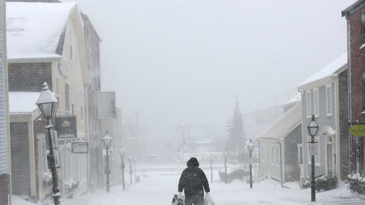 A woman walks down the street in New Bedford, Mass., on Monday, Feb. 8, 2016 during a snowstorm. The second winter storm in four days to hit the Northeast is expected to bring blizzard conditions to Cape Cod and southeastern Massachusetts and leave behind as much as 18 inches of snow.