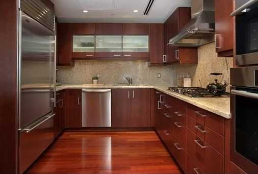 A custom Poggen Pohl kitchen has top-of-the-line appliances, bounds of storage and a breakfast bar open to the living and dining area.