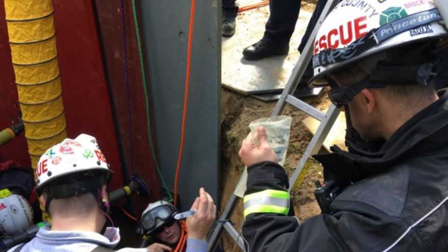 Paramedics start an IV on the victim in the hole as they work to free him.