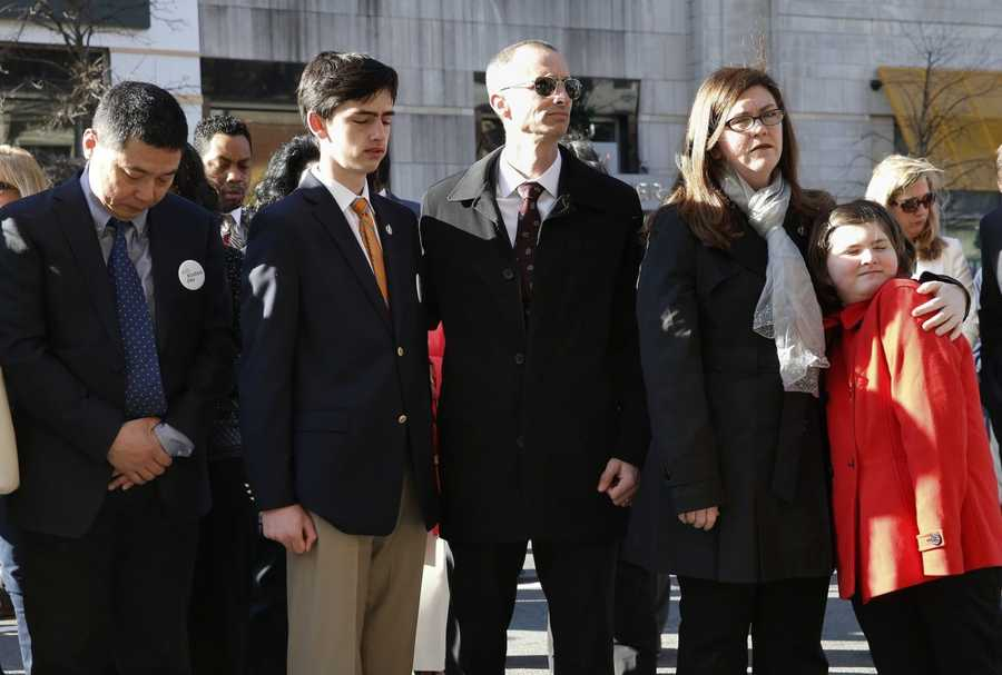 Family members of Boston Marathon bombing victim Martin Richard, Bill, third from right, Denise, second from right, Jane, right, and Henry, second from left, along with the father of victim Lingzi Lu, Jun Lu, left, pause after placing a wreath on the third anniversary of the bombings, Friday, April 15, 2016, in Boston.