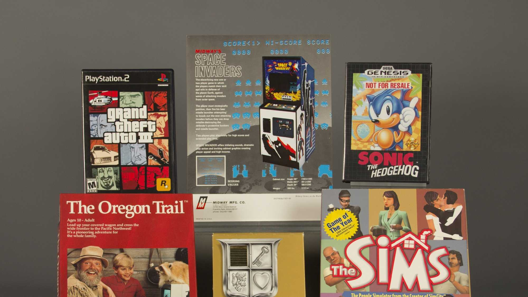 "In this April 21, 2016 photo provided by The Strong museum in Rochester, N.Y., the 2016 inductees to the World Video Game Hall of Fame are displayed. From top left, clockwise, are ""Grand Theft Auto III,"" ""Space Invaders,"" ""Sonic the Hedgehog,"" ""The Sims,"" ""The Legend of Zelda,"" and ""The Oregon Trail."""