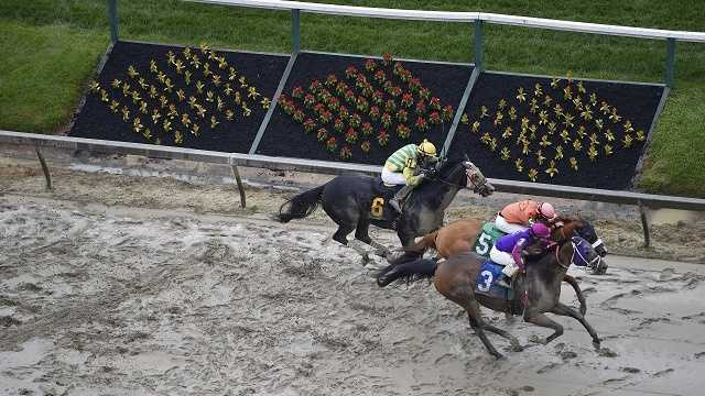 Homeboykris (3), ridden by Horacio Karamanos, wins the first race of the day on a muddy track ahead of the 141st Preakness Stakes horse race at Pimlico Race Course, Saturday, May 21, 2016, in Baltimore.