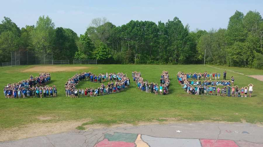 "Students at Ruggles Lane School, where the officer's wife, works spell out ""Love."""