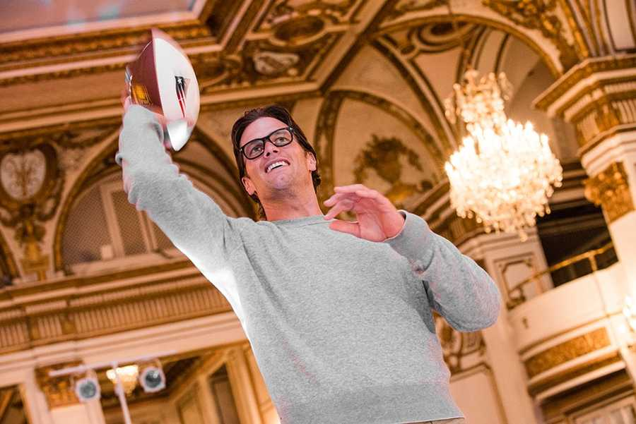 Tom Brady throws a pass to a donor willing to pledge $5,000 to the cause.