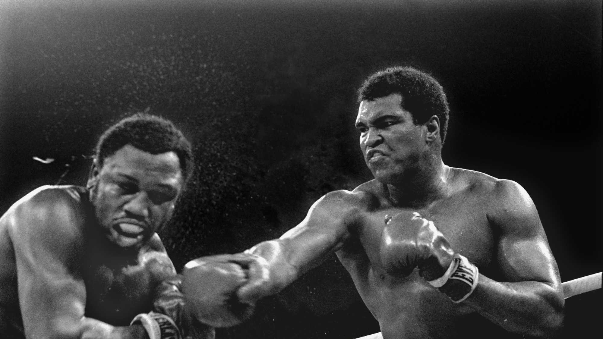 Spray flies from the head of challenger Joe Frazier as heavyweight champion Muhammad Ali connects with a right in the ninth round of their title fight in Manila, Philippines, October 1, 1975. Ali won the fight on a decision to retain the title.