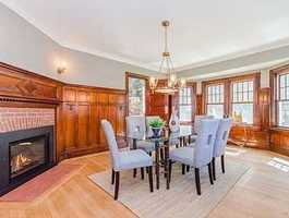 A dining room perfect for entertaining, with restored woodwork an elegant gas fireplace.