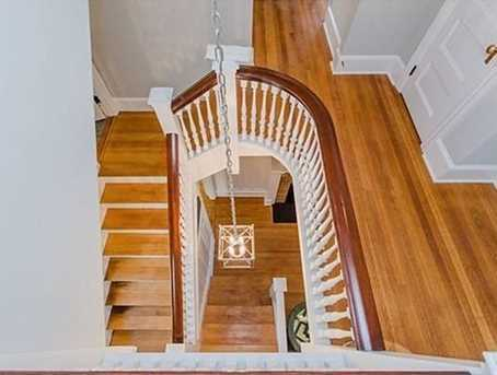 Welcoming foyer w/ gas fireplace & built-ins featuring a beautiful curved staircase.