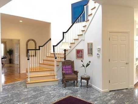 The two story foyer with its rich marble floor and beautiful stairwell bathes in the glow of the skylights above and sets the tone. From there, you travel through a lovely living room with its wall of windows to a very large dining room.