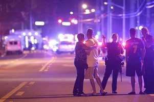 Orlando Police officers direct family members away from a fatal mass shooting at Pulse Orlando nightclub in Orlando, Fla., Sunday, June 12, 2016.