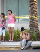 People wait outside the emergency entrance of the Orlando Regional Medical Center hospital after a shooting involving multiple fatalities at Pulse Orlando nightclub in Orlando, Fla., Sunday, June 12, 2016.