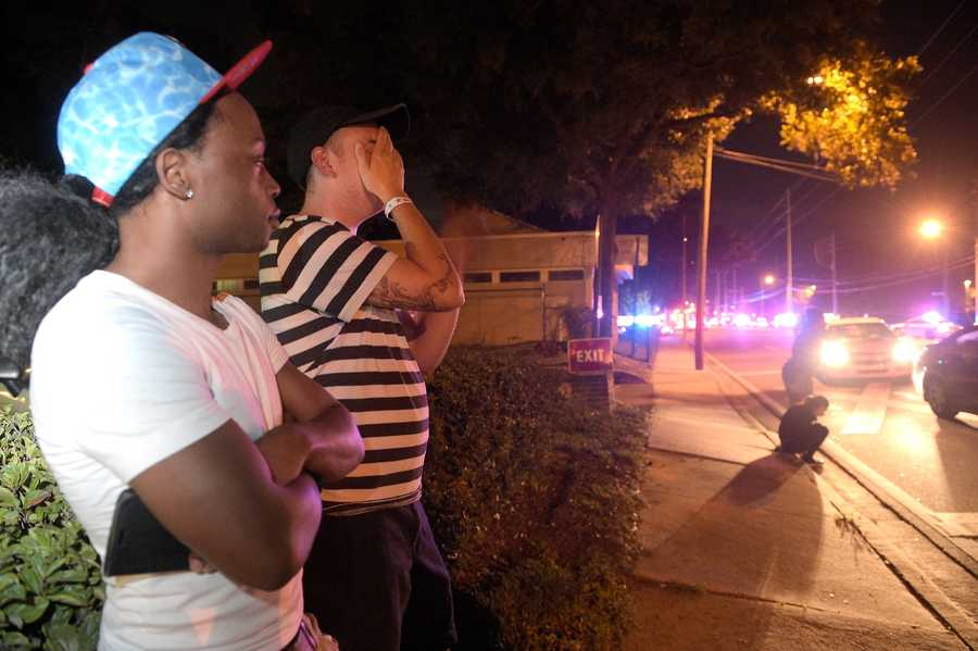 Jermaine Towns, left, and Brandon Shuford wait down the street from a multiple shooting at a nightclub in Orlando, Fla., Sunday, June 12, 2016. Towns said his brother was in the club at the time. A gunman opened fire at a nightclub in central Florida, and multiple people have been wounded, police said Sunday.
