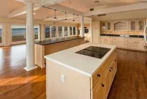 Spacious kitchen and living room with soaring ceilings, a wall of doors and windows providing natural light and a stone fireplace opening to the deck on the ocean side.