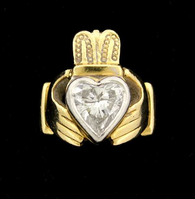 A gold claddagh ring with a heart-shaped diamond