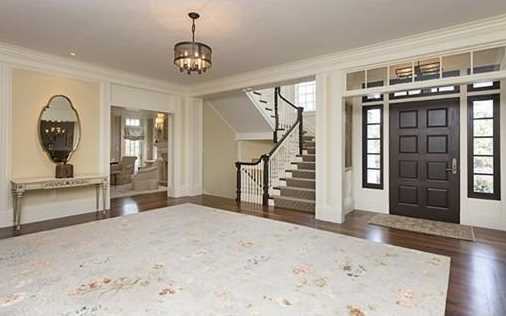 A grand foyer opens to a formal living room w/ fireplace, a dining room w/ expansive bay, & partners office w/ fireplace.