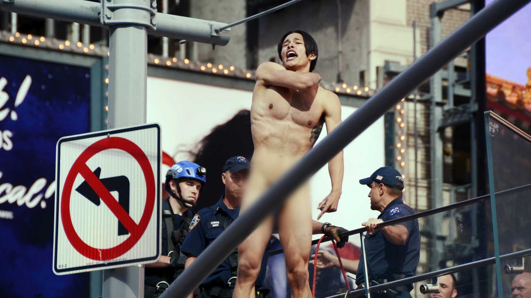 A naked man shouts before jumping from the ledge above the TKTS Broadway ticket booth in New York's Times Square, Thursday, June 30, 2016. Police said the man, who was shouting about presumptive Republican presidential nominee Donald Trump, was conscious after the jump of about 16 feet off the booth.