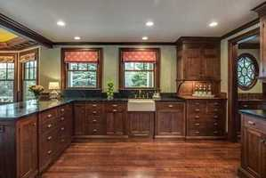 Richly finished Kitchen with milled cabinetry, dumbwaiter to service Kitchen and cozy Family Room with coffered ceiling.