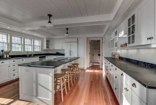 The fantastic Cook's Kitchen is bright and airy, with requisite high-end appliances, center island, soapstone counters and a French door leading to a deck, the perfect spot for afternoon sundowners.