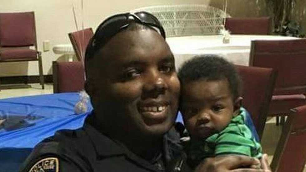 In this 2016 photo provided by Trenisha Jackson, her husband, Baton Rouge Police Officer Montrell Jackson, holds his son Mason at a Father's Day event for police officers in Baton Rouge, La. Montrell Jackson and two other Baton Rouge law enforcement officers investigating a report of a man with an assault rifle were killed Sunday, less than two weeks after a black man was fatally shot by police here in a confrontation that sparked nightly protests that reverberated nationwide.
