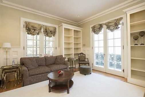 The detailed & formal fireplaced living room has a built-in bench seating area & french doors leading to the covered porch.
