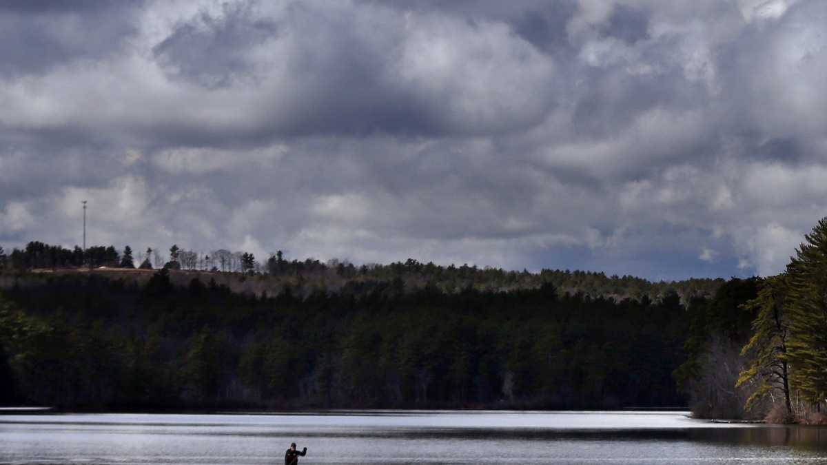 Storm clouds build prior to the arrival of a thunderstorm as Jeff Warren of Auburn, Maine, heads for shore on his paddleboard on Lower Range Pond Thursday, March 17, 2016, in Poland, Maine.