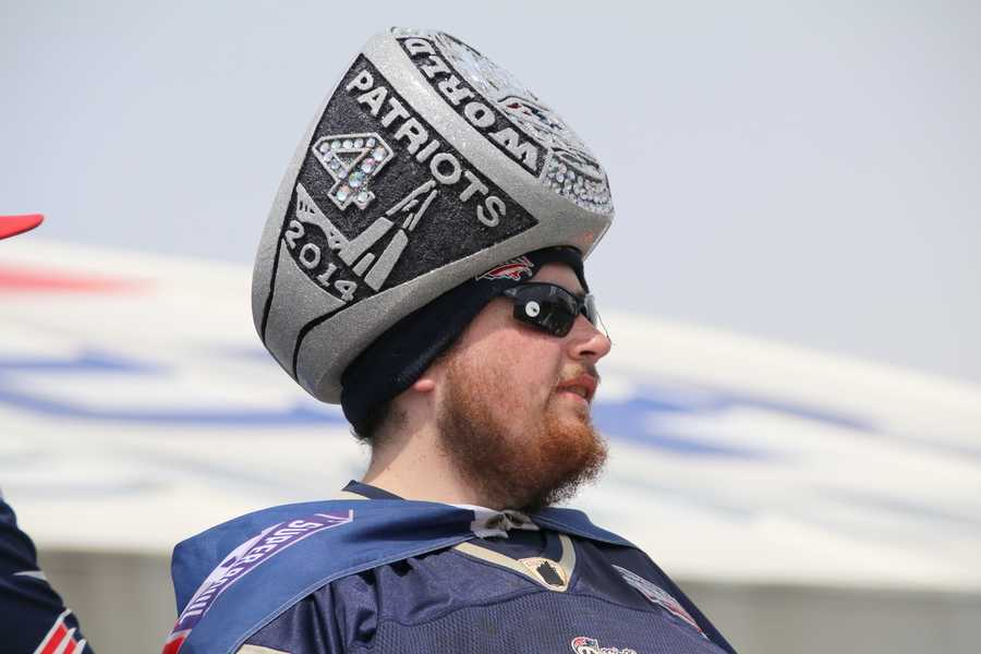 A Patriots fan wearing a Super Bowl ring hat watches the team as they practice.