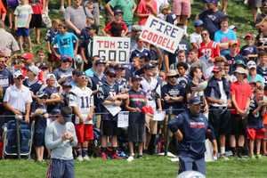 Patriots fans cheer on the team as the team runs plays during practice.