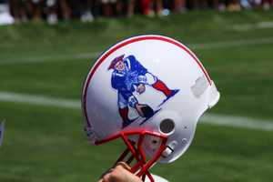 A fan holds up an original New England Patriots helmet during training camp.