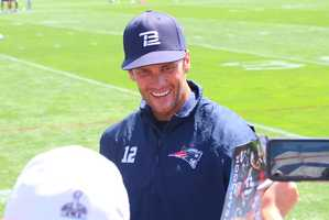Fans cheered as Tom Brady signed autographs after practice on Saturday.