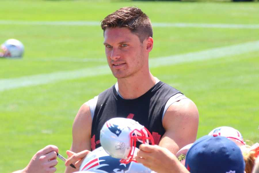 Patriots wide receiver Chris Hogan signs autographs following the team's practice on Saturday.