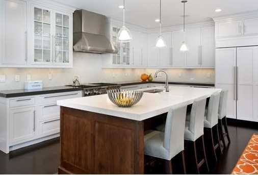 Stunning kitchen features a sleek island, professional appliances and sun-splashed breakfast room.