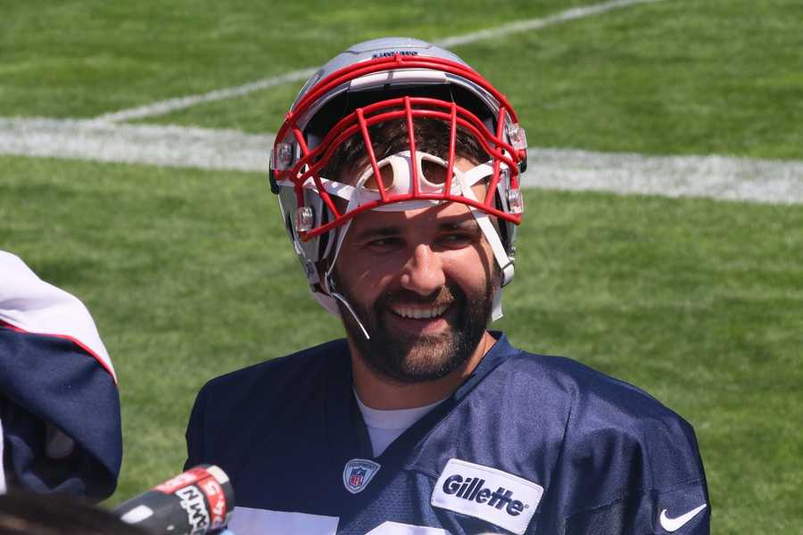 Patriots defensive end Rob Ninkovich smiles as he signs autographs for fans after the team's practice Monday.