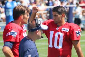 Patriots quarterbacks Tom Brady and Jimmy Garoppolo talk on the sidelines after a series against the Saints.