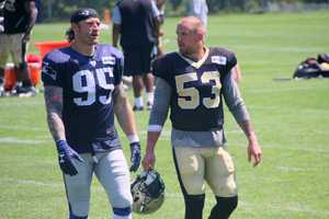 Patriots defensive end Chris Long chats with Saints linebackr JamesLaurinaitis at the end of practice Tuesday. The two played together in St. Louis last year.
