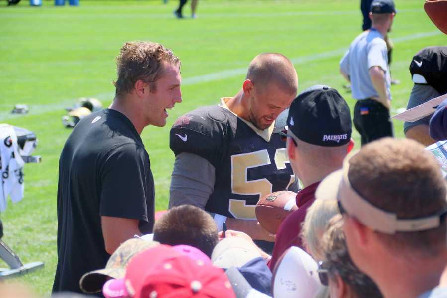 Players for the Saints sign autographs for Patriots fans and Saints fans after practice.