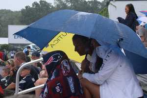 Many fans watching practice remained during the downpours, pulling out ponchos and umbrellas to take cover.