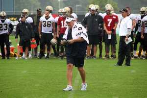 Patriots head coach Bill Belichick reviewing plays during a rainy practice session.