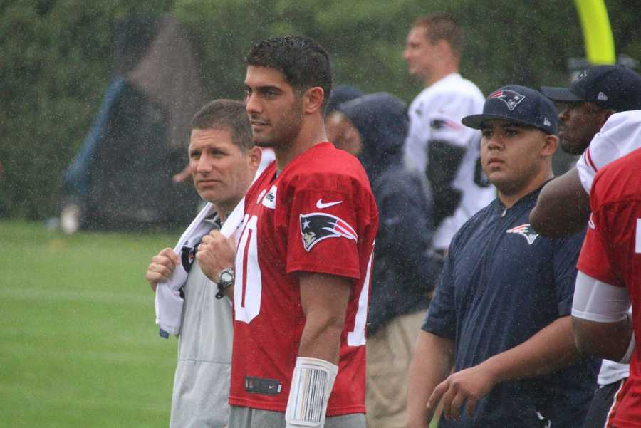Patriots quarterback Jimmy Garoppolo watches action on the field during a heavy rain shower.