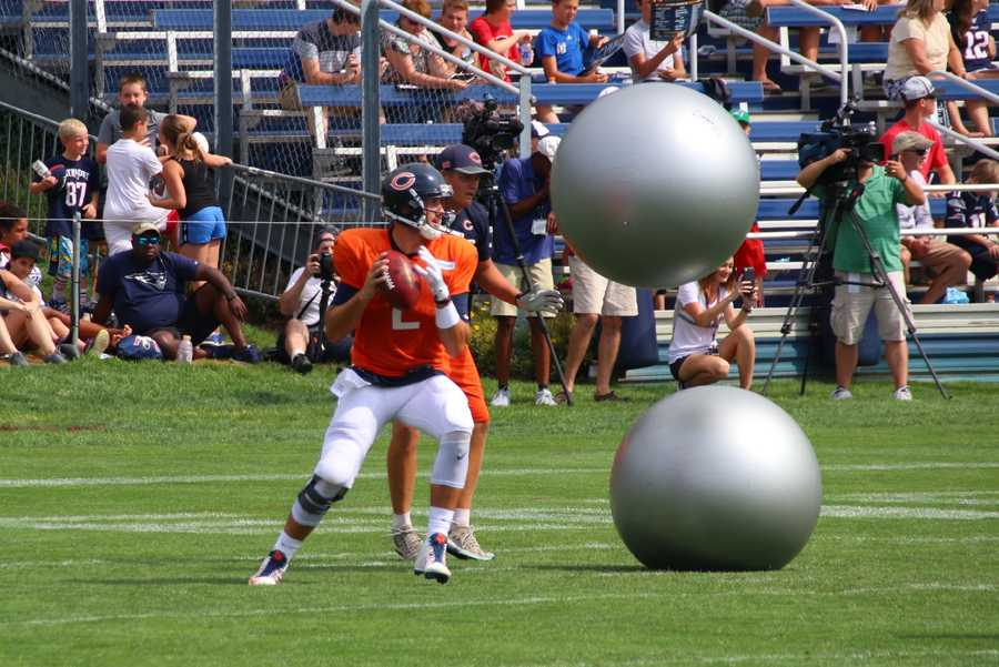 During individual team drills, trainers throw big balls at Bears quarterbacks, trying to complete passes downfield.