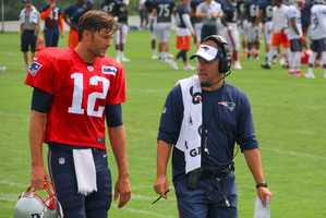 Patriots quarterback Tom Brady and offensive coordinator Josh McDaniels chat at practice.