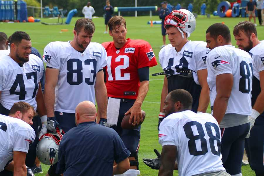 Patriots quarterback Tom Brady listens as receivers chat on the sidelines.
