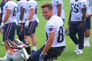 Patriots wide receiver Danny Amendola smiles for the crowd as he works out on an exercise bike on the field.
