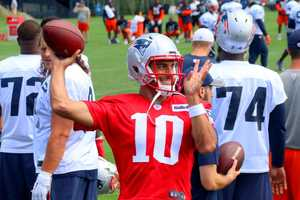 Patriots quarterback Jimmy Garoppolo tosses passes on the sidelines while the defense works on the field.