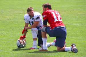 Julian Edelman and Tom Brady chat while the defense is on the field.